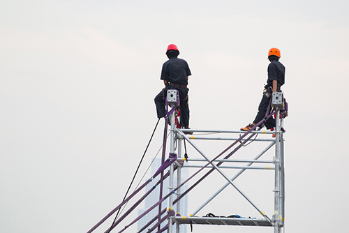 Construction workers working on scaffolds