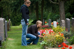 Photo of grieving sisters at a cemetery
