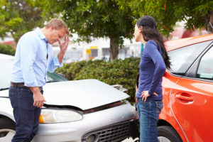 Two Drivers Arguing After Traffic Accident With Head In Hands.