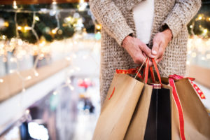 senior woman with paper bags doing Christmas holiday shopping.